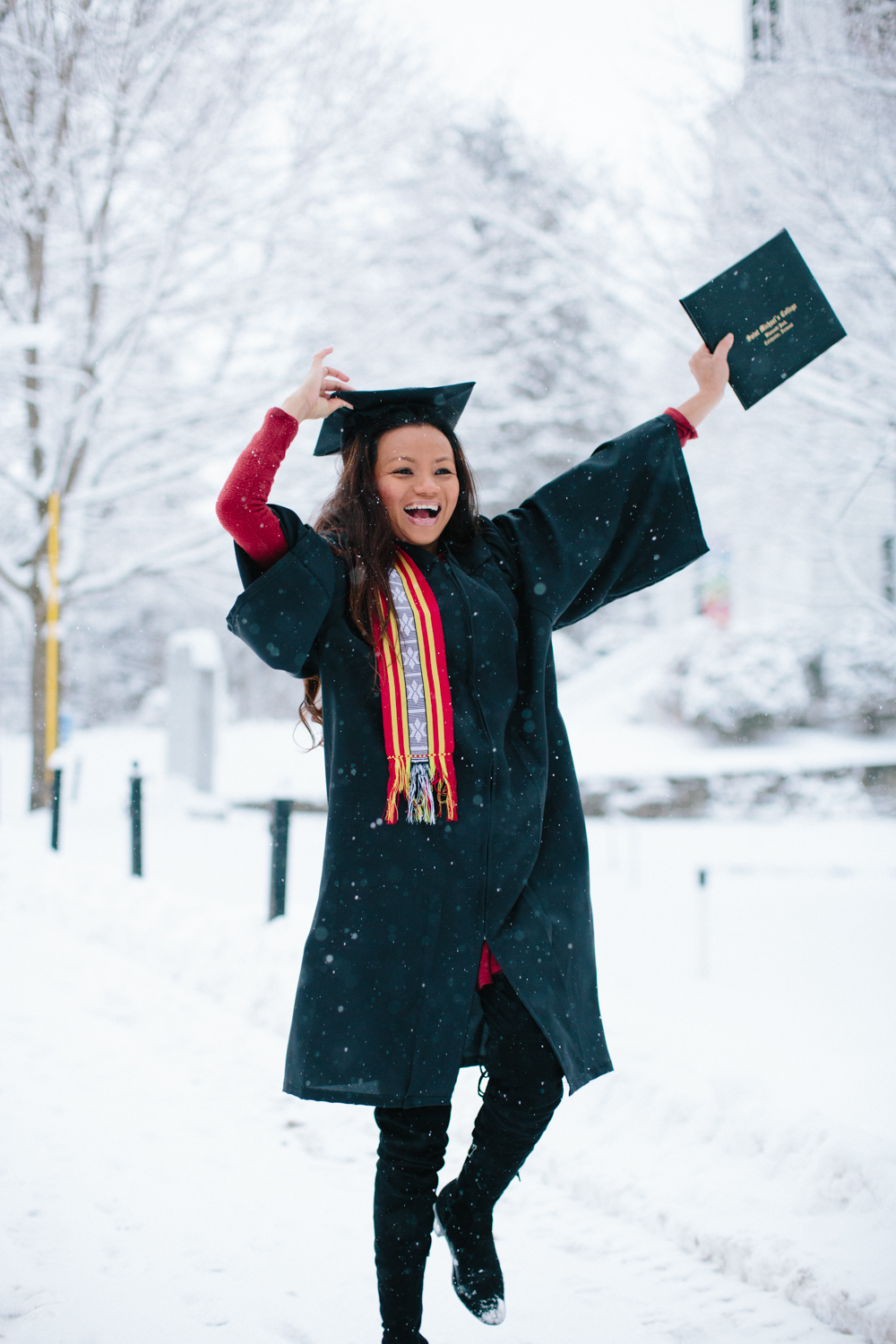Rania, wearing a cap and gown, dancing in the snow with her diploma celebrating graduation